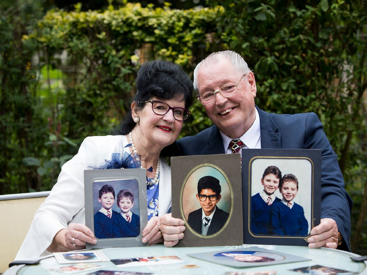 Neville and Gillian Howe looking back over old photos of children they have cared for.