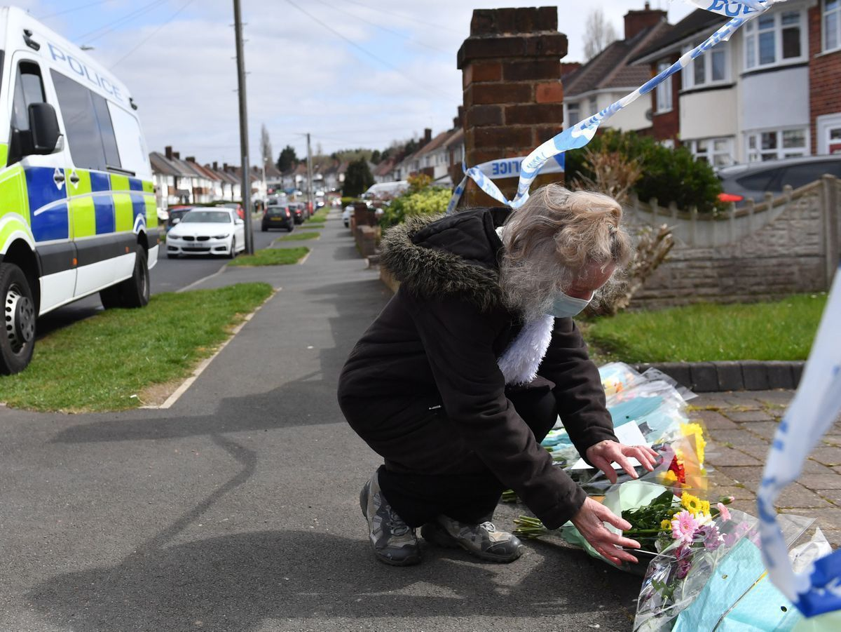 A woman puts flowers down outside the house on Boundary Avenue