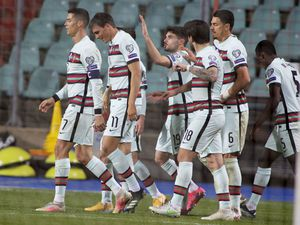 Portugal's Joao Palhinha, second left, is congratulated by teammates after scoring his sides third goal during the World Cup 2022 group A qualifying soccer match between Luxembourg and Portugal at the Josy Barthel Stadium in Luxembourg, Tuesday, March 30, 2021. (AP Photo/Olivier Matthys).