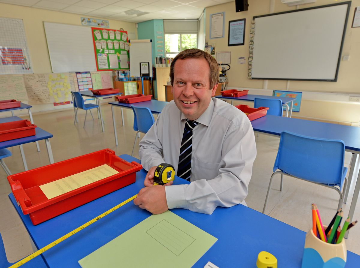 Andrew Clewer, headteacher at Landywood Primary School, measuring out desks in a classroom