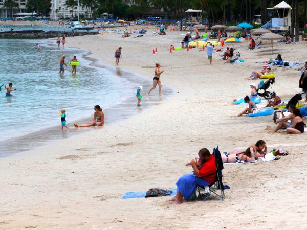 People sit on Waikiki Beach in Honolulu