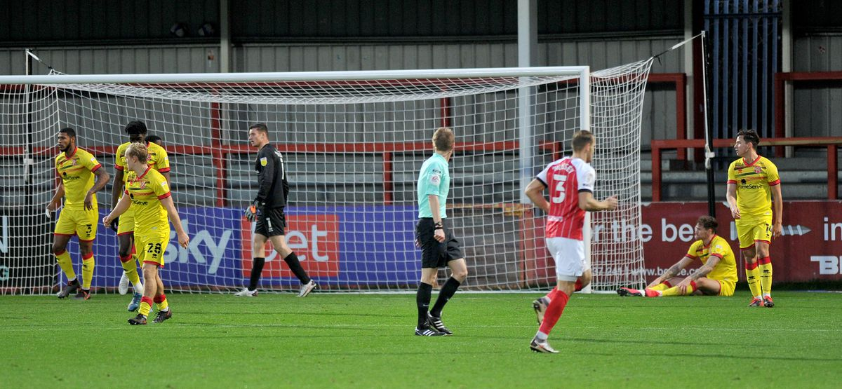 The ball hits Dan Scarr(seated)for an own goal