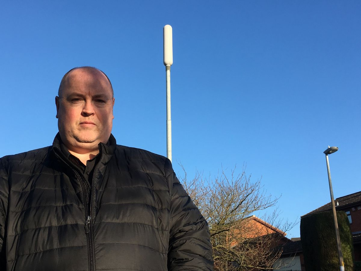 Councillor Shaun Keasey in front of the current 14m mast on Gospel End Road