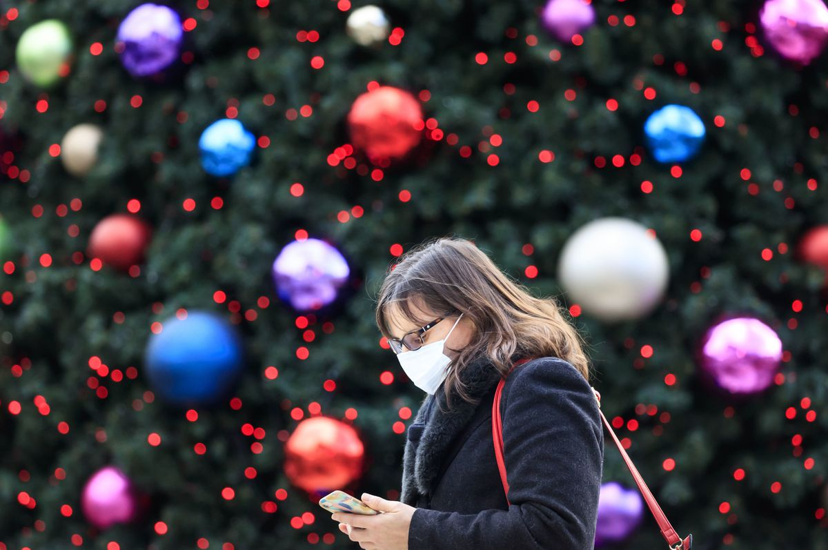 A woman walks past a Christmas tree during lockdown.