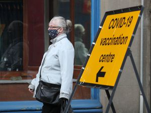 A member of the public passes a COVID-19 vaccination centre sign in Blairgowrie. Picture date: Saturday March 27, 2021. PA Photo. See PA story SCOTLAND Coronavirus. Photo credit should read: Andrew Milligan/PA Wire.
