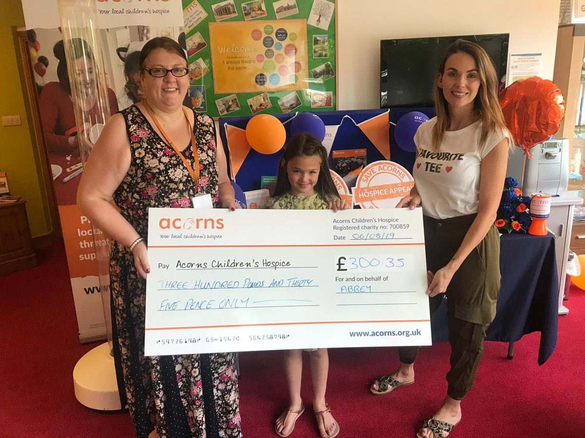 Abigail and Rebecca present their donation to Acorn Hospice