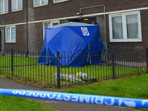 Flowers behind the police cordon at the scene of the murder in Heath Town