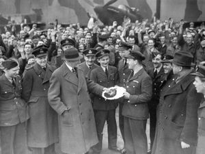 "A silver salver is presented to Flight Lieutenant ""Tommie"" Thomas to the cheers of Wolverhampton workers"