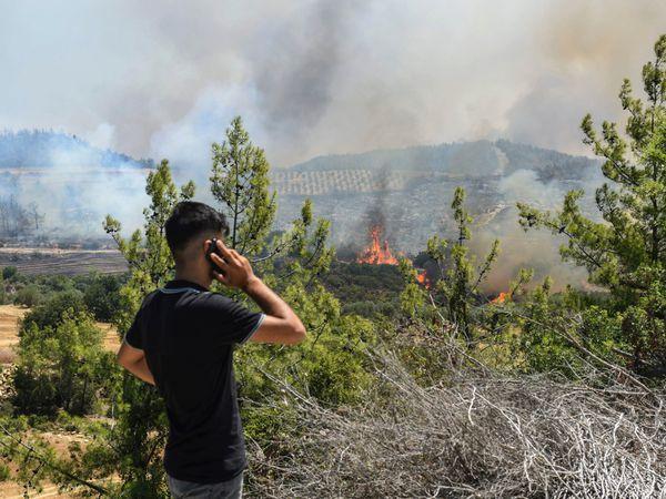 A man watches wildfires in Antalya, Turkey