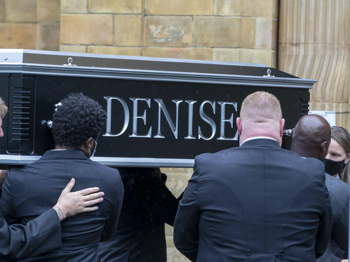 People carry the coffin outside Manchester Crematorium