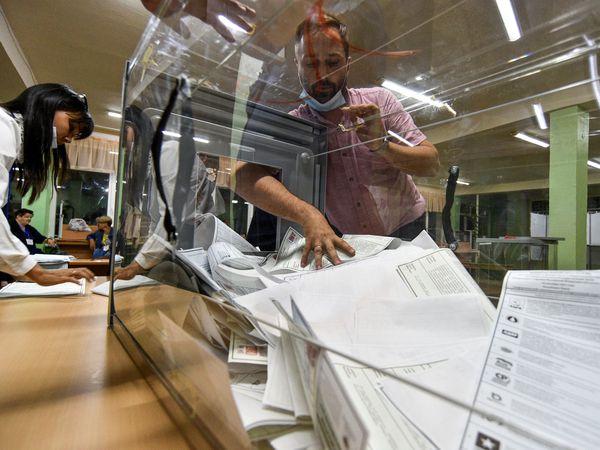 Someone puts ballots into a box