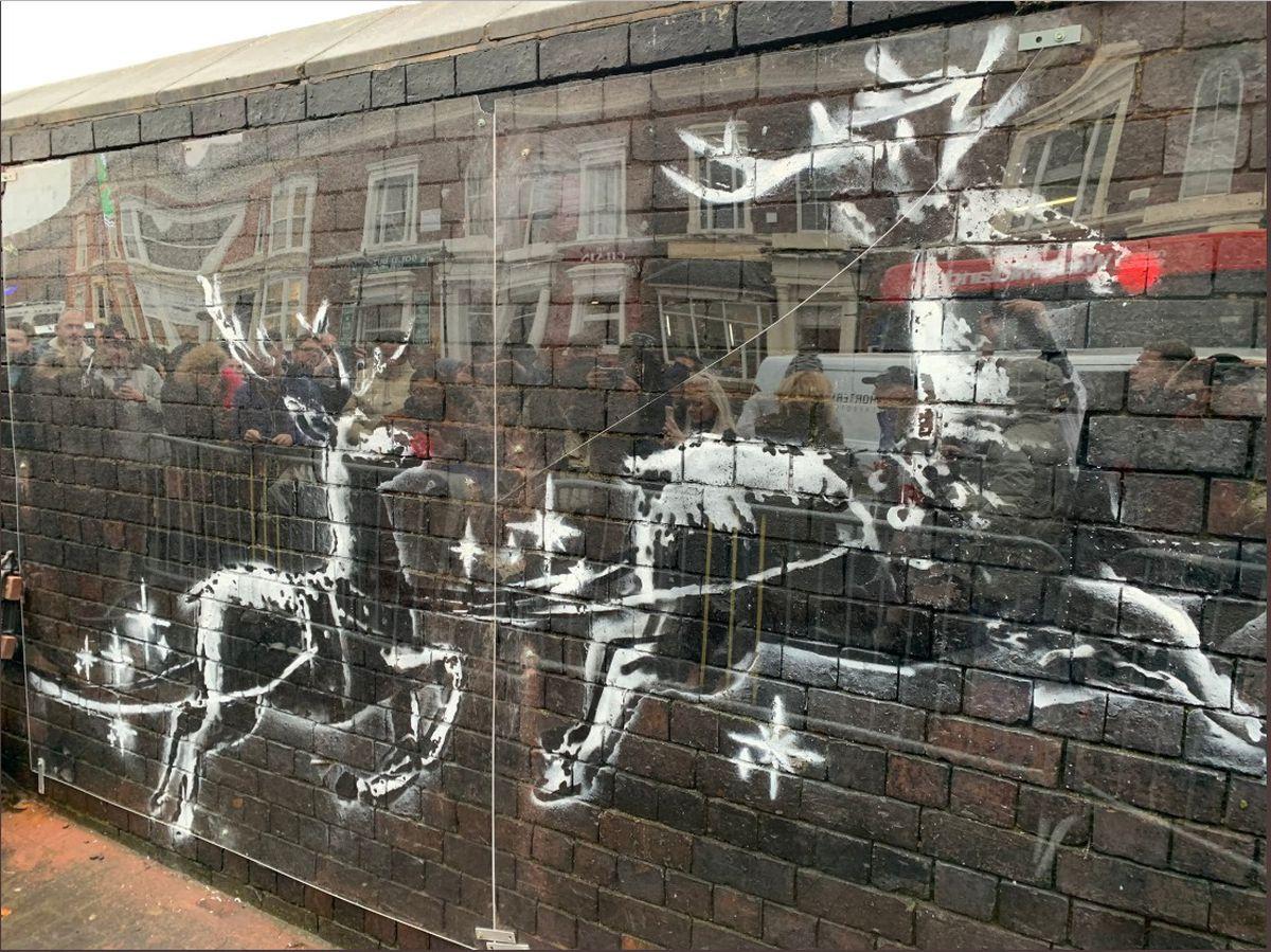 The vandalised Banksy artwork in Birmingham now protected by perspex glass. Photo from Twitter @philmackie