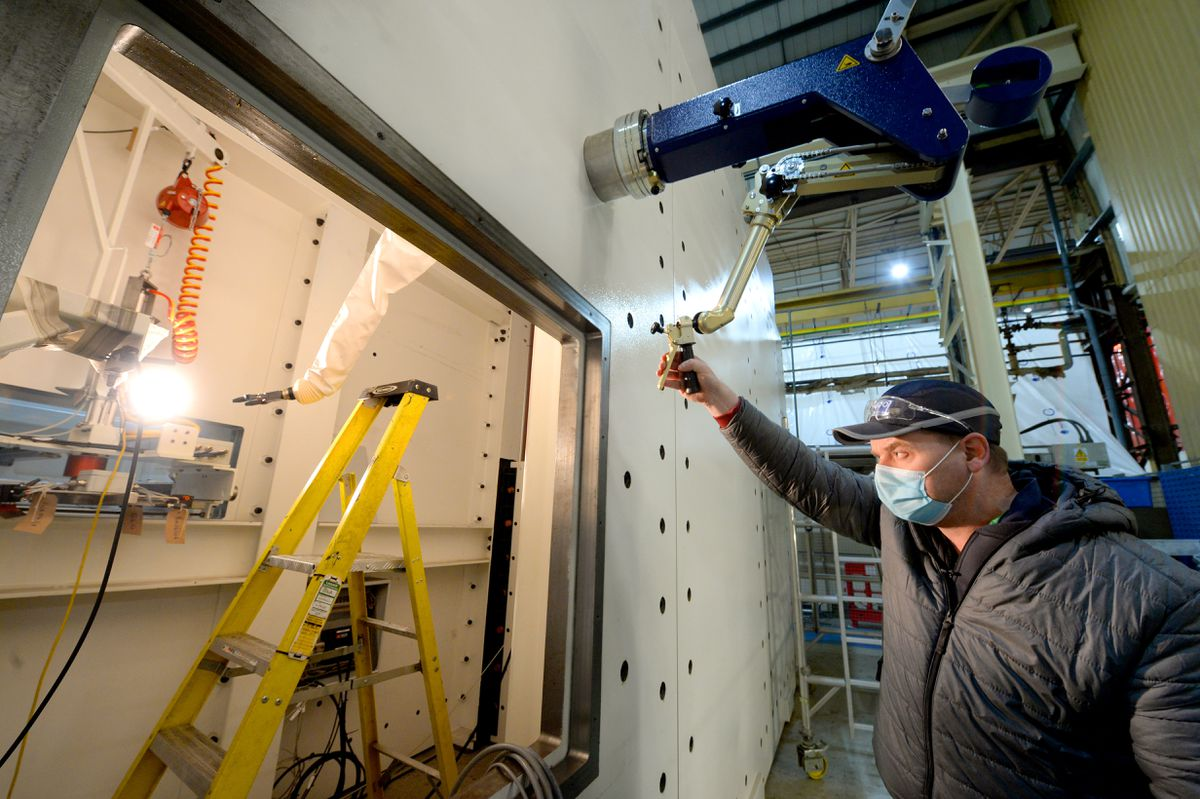 Cell leader Pete Andrews demonstrates the manipulator, a robotic arm for handling nuclear waste
