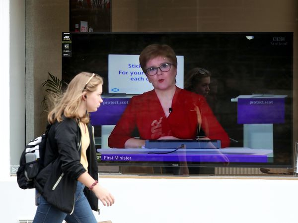 A woman walks past Nicola Sturgeon on TV