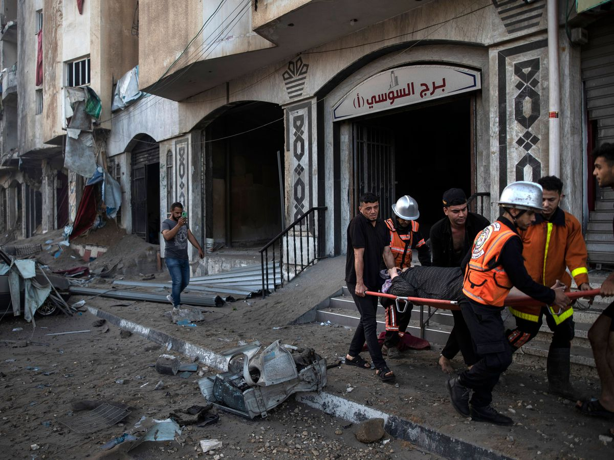 Palestinian rescuers evacuate an elderly woman in Gaza City