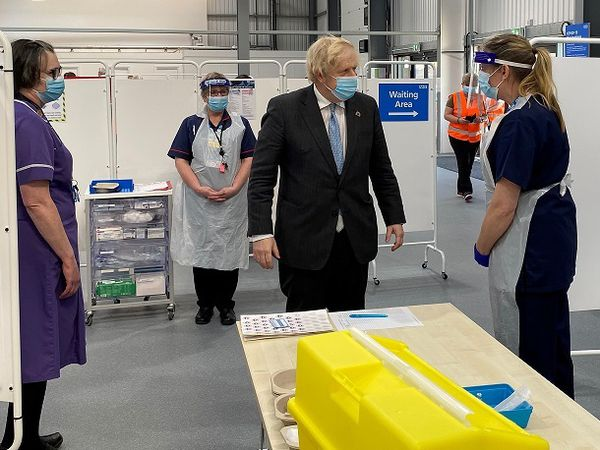 Prime Minister Boris Johnson chats to staff and volunteers during a visit to Tunstall Covid-19 Vaccination Centre