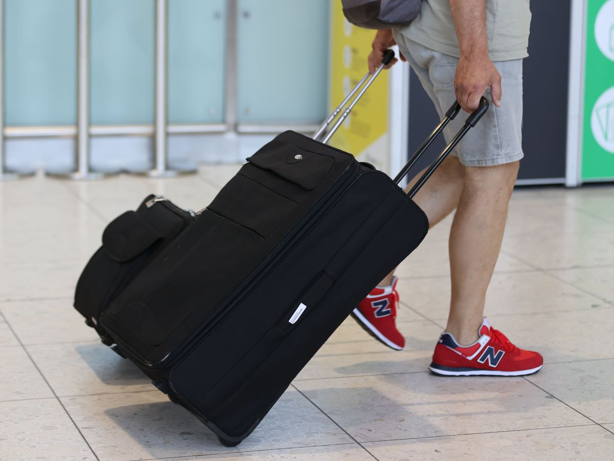 A passenger with a suitcase at an airport