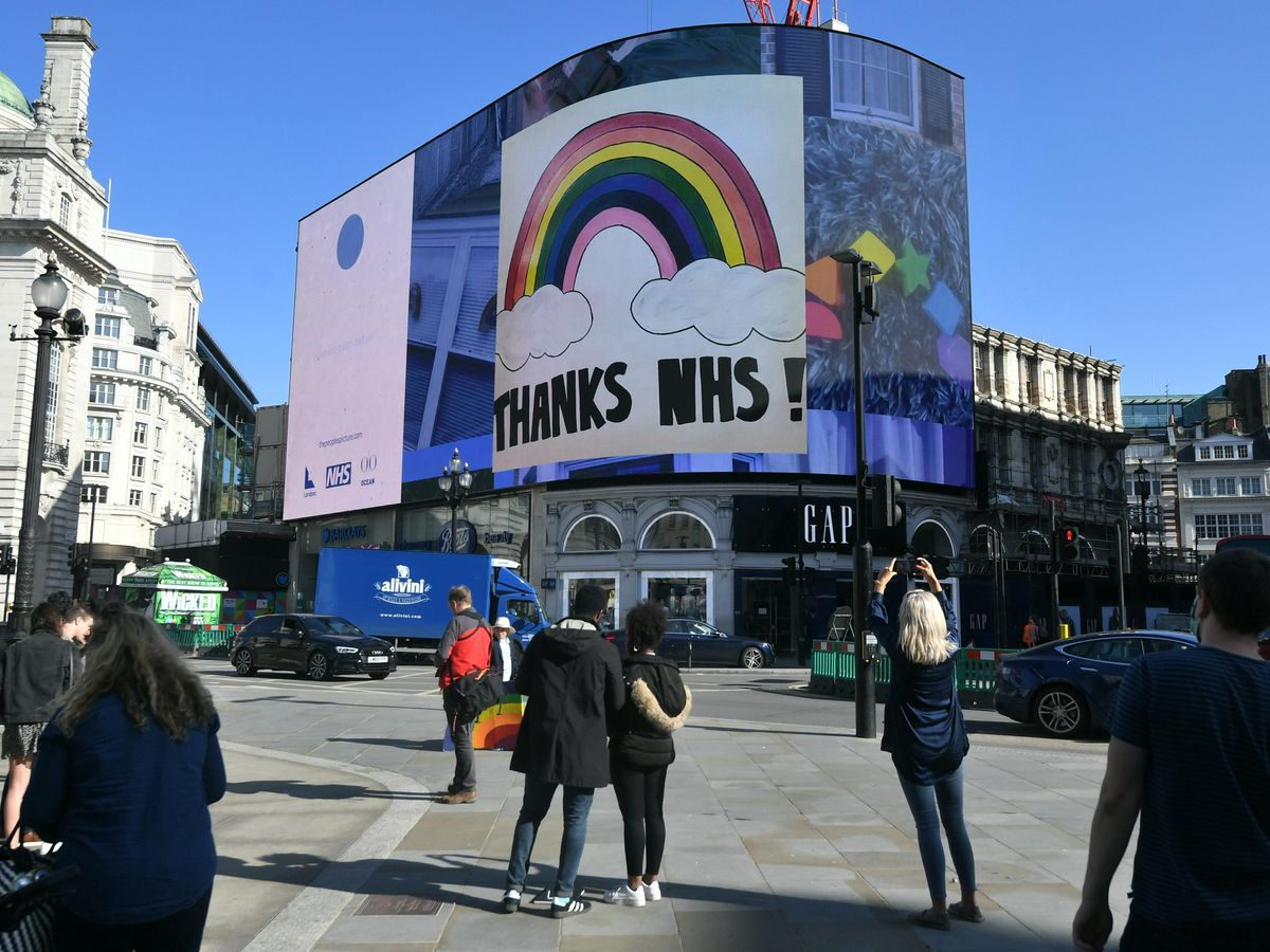 Members of the public take photographs of the Piccadilly Lights new interactive mosaic art project, Rainbows for the NHS, in Piccadilly Circus, London.