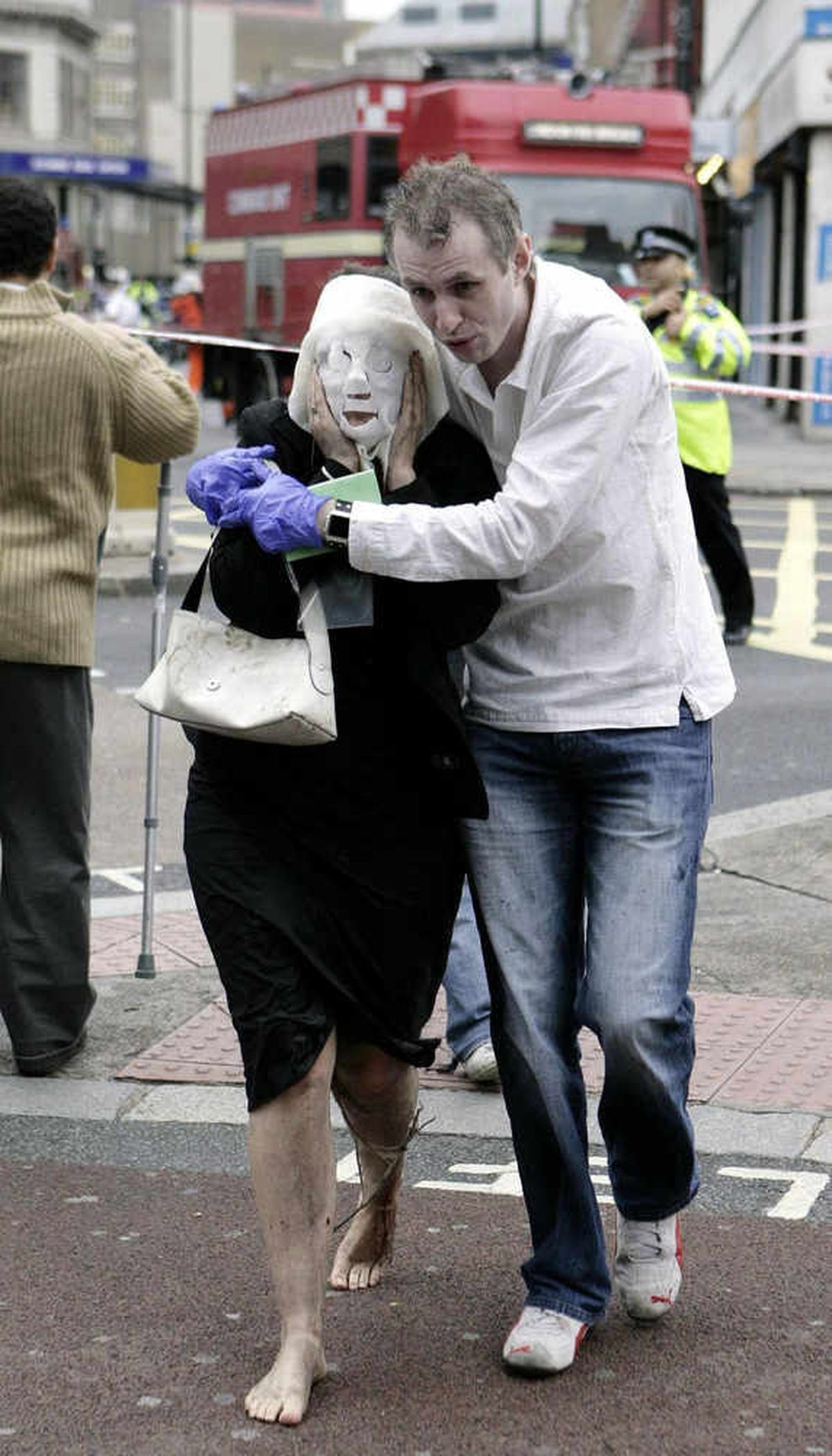 Paul leads Davinia Turrell, wearing a surgical burns mask, to safety after the Edgware Road blast