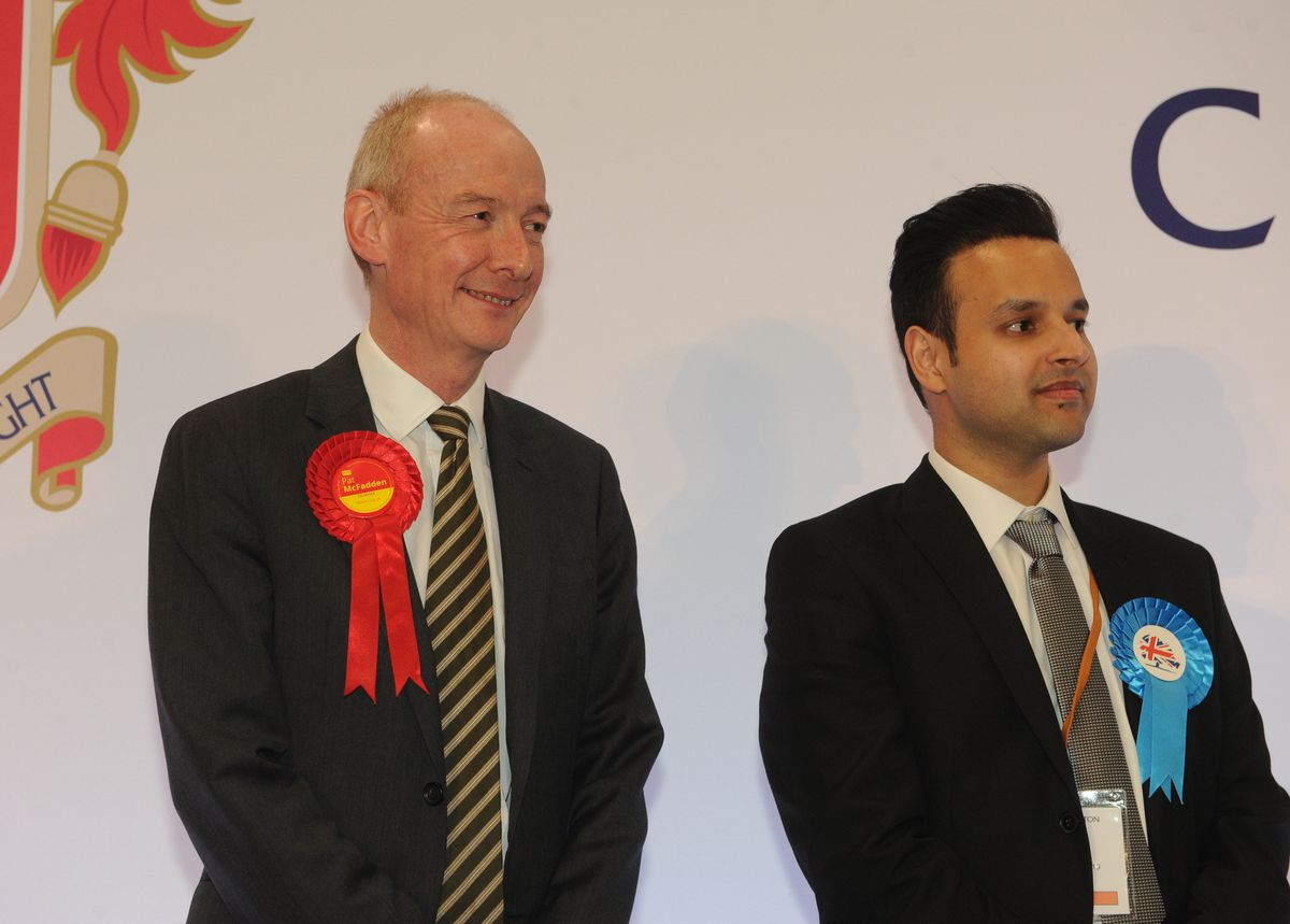 Pat McFadden, left, smiles after defeating Tory candidate Ahmed Ejaz, right