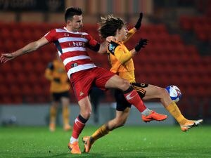 """Doncaster Rovers' Andy Butler (left) and Wolverhampton Wanderers' Fabio Silva battle for the ball during the Papa John's Trophy Group F match at Keepmoat Stadium, Doncaster. PA Photo. Picture date: Tuesday November 10, 2020. See PA story SOCCER Doncaster. Photo credit should read: Mike Egerton/PA Wire. RESTRICTIONS: EDITORIAL USE ONLY No use with unauthorised audio, video, data, fixture lists, club/league logos or """"live"""" services. Online in-match use limited to 120 images, no video emulation. No use in betting, games or single club/league/player publications.."""