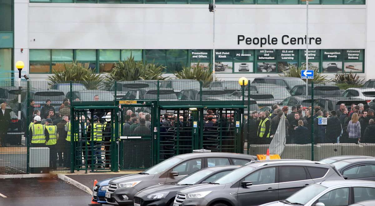 Staff gather outside the JLR site in Halewood, Merseyside, on Thursday