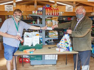 David Clarke of Lichfield Foodbank, left, receives a cheque from Trevor James of Lichfield St Chad Rotary Club.(Picture by Robert Yardley)