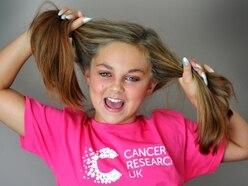 Schoolgirl in headshave for children's wig charity
