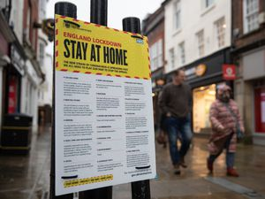 People walk past a Government sign warning people to stay at home on the High Street in Winchester, Hampshire