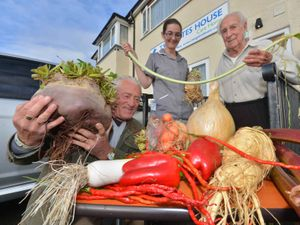 Mick Poultney from Colley Gate with former veg grower Derrick Morris, 95, and care assistant Hayli Belcher. They are holding a blanche leek
