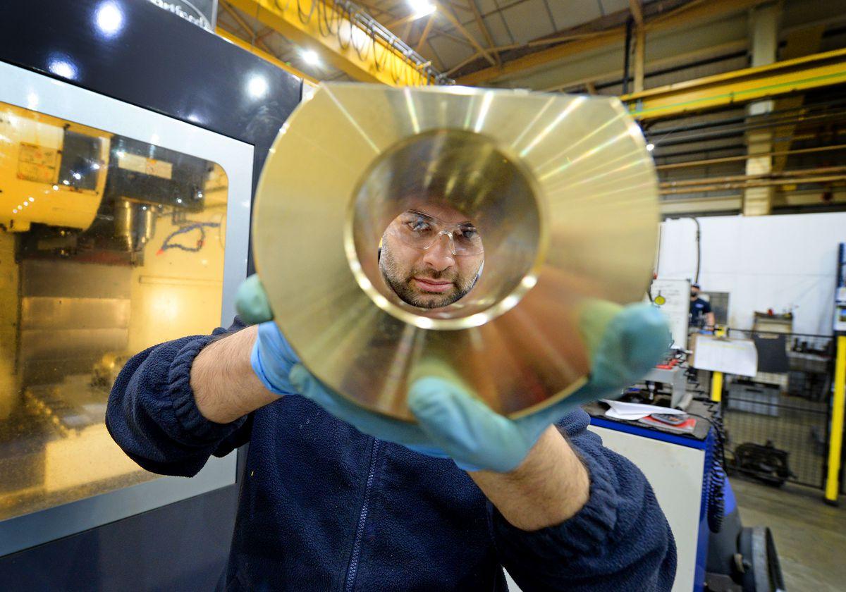 Machinist Chris Moore checks a brass pivot sleeve at Ansaldo Nuclear