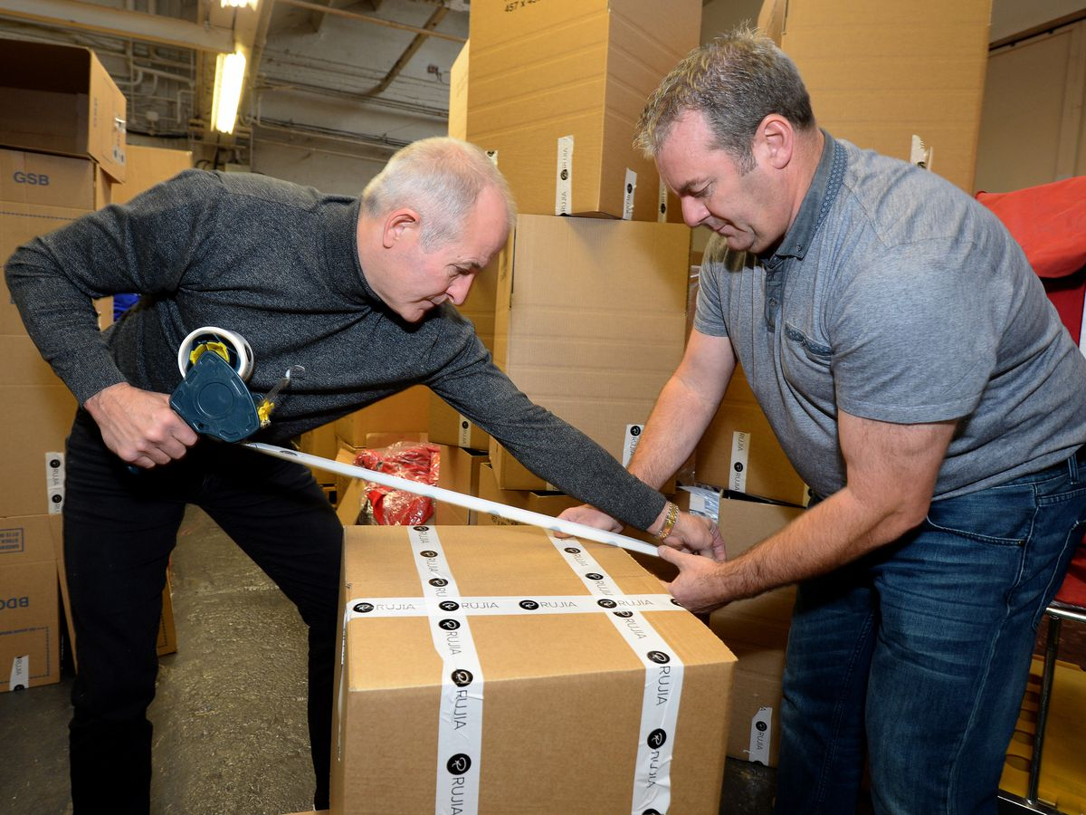Steve Bull and fellow volunteer Bryn Jeavons tape up a box as part of the Steve Bull Foundation initiative