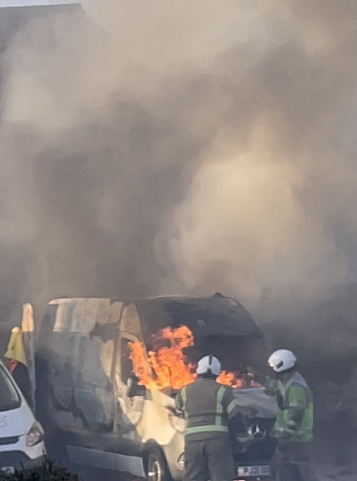 Firefighters work to extinguish the fire engulfing a van in Pencombe Drive
