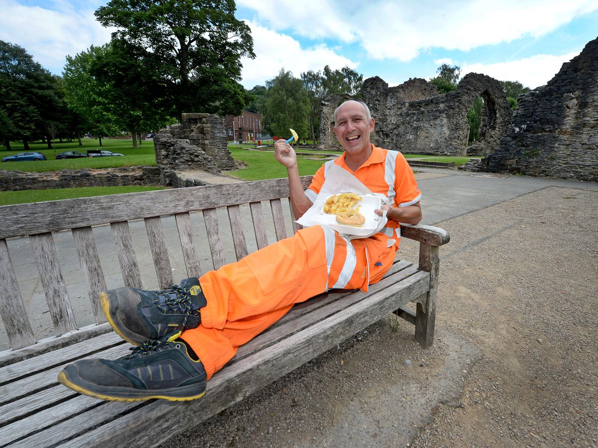 Robert Edwards enjoys his lunch break in the sunshine and a bag of chips on a wooden bench in the beautiful Priory Park, Dudley