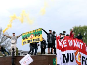 """File photo dated 02-05-2021 of Fans holding up banners as they protest against the Glazer family, the owners of Manchester United, before their Premier League match against Liverpool at Old Trafford, Manchester. Issue date: Wednesday May 5, 2021. PA Photo. Ole Gunnar Solskjaer reiterated the need for Manchester United supporters to be listened to, but said protests had to be """"civilised"""" after Sunday's anti-Glazer demonstration forced the clash against Liverpool to be called off. See PA story SOCCER Man Utd. Photo credit should read Barrington Coombs/PA Wire.."""