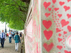 Pedestrians walk past the Covid memorial wall in Westminster