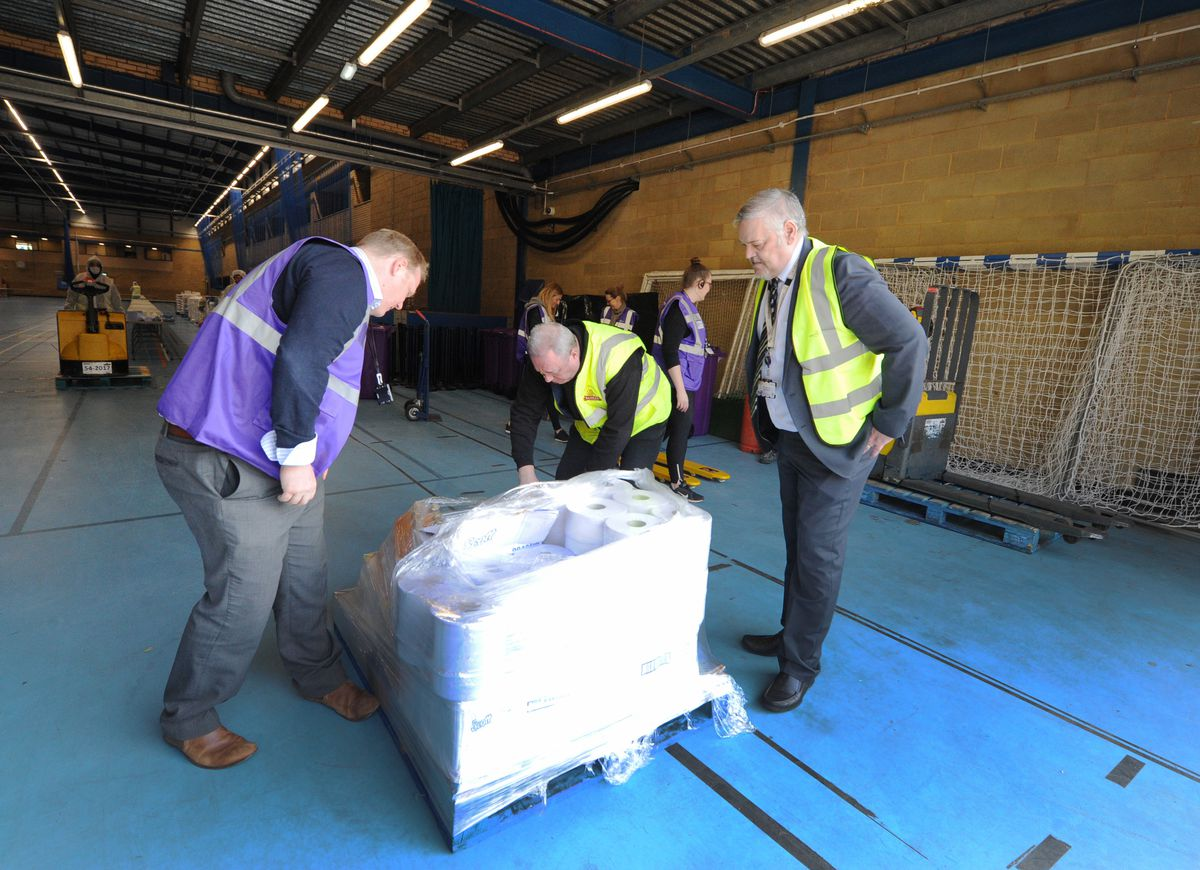 Council officers setting up equipment at the distribution centre, observed by Ian Brookfield
