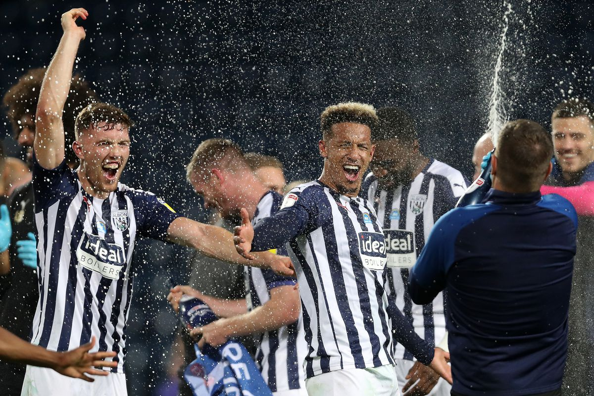 Dara O'Shea of West Bromwich Albion and Callum Robinson of West Bromwich Albion spray champagne as he celebrates promotion to the Premier League on the pitch at the end of the match. (AMA)
