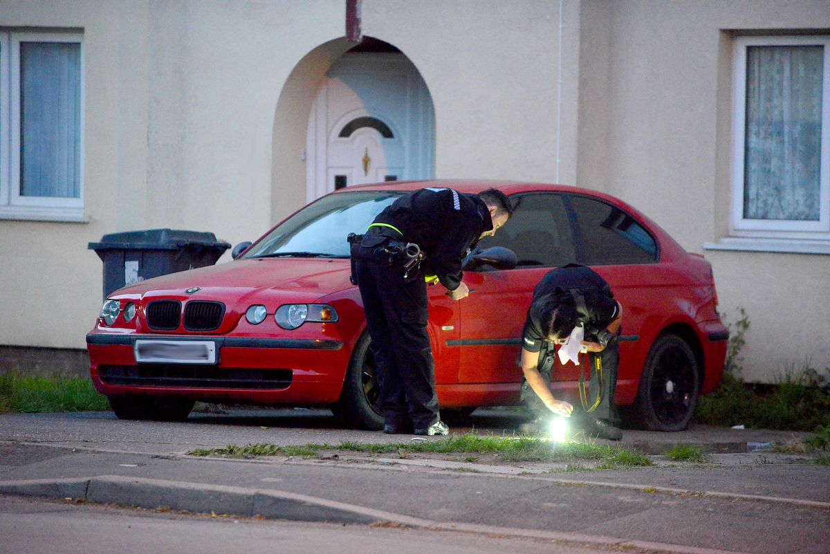 Police scoured the area around this red BMW in Legge Street in the aftermath of the gunfire