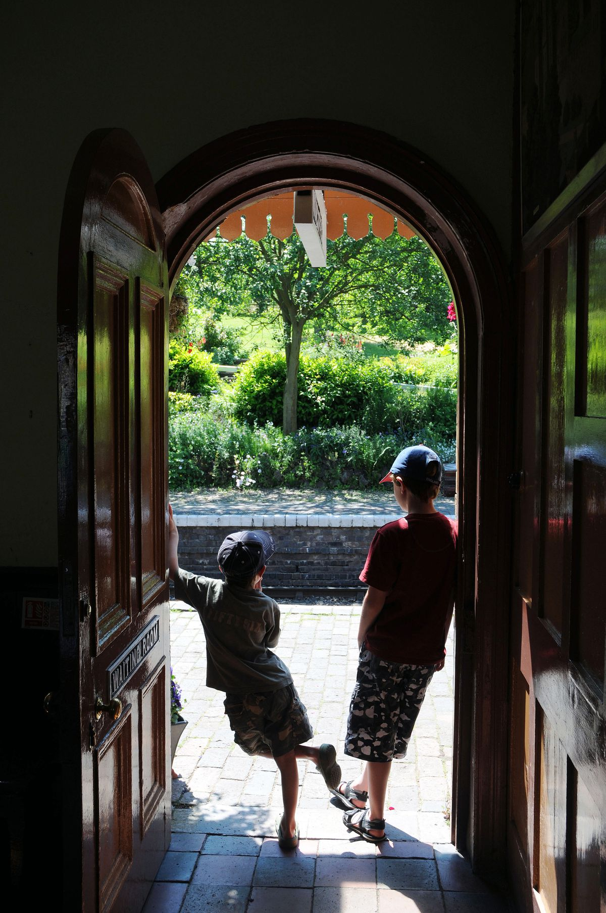 Two lads at the door of the waiting room at Arley Station Worcestershire on the Severn Valley Railway.