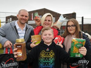 Shaun Ruby, Kim Ruby, Lauren Ruby and (front) Craig Ruby pose outside Craig's school, Beacon Primary school in Willenhall with some of the bags of food donated