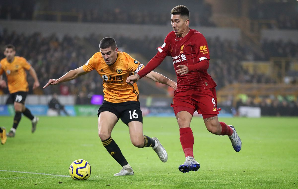 Conor Coady (left) and Liverpool's Roberto Firmino battle for the ball