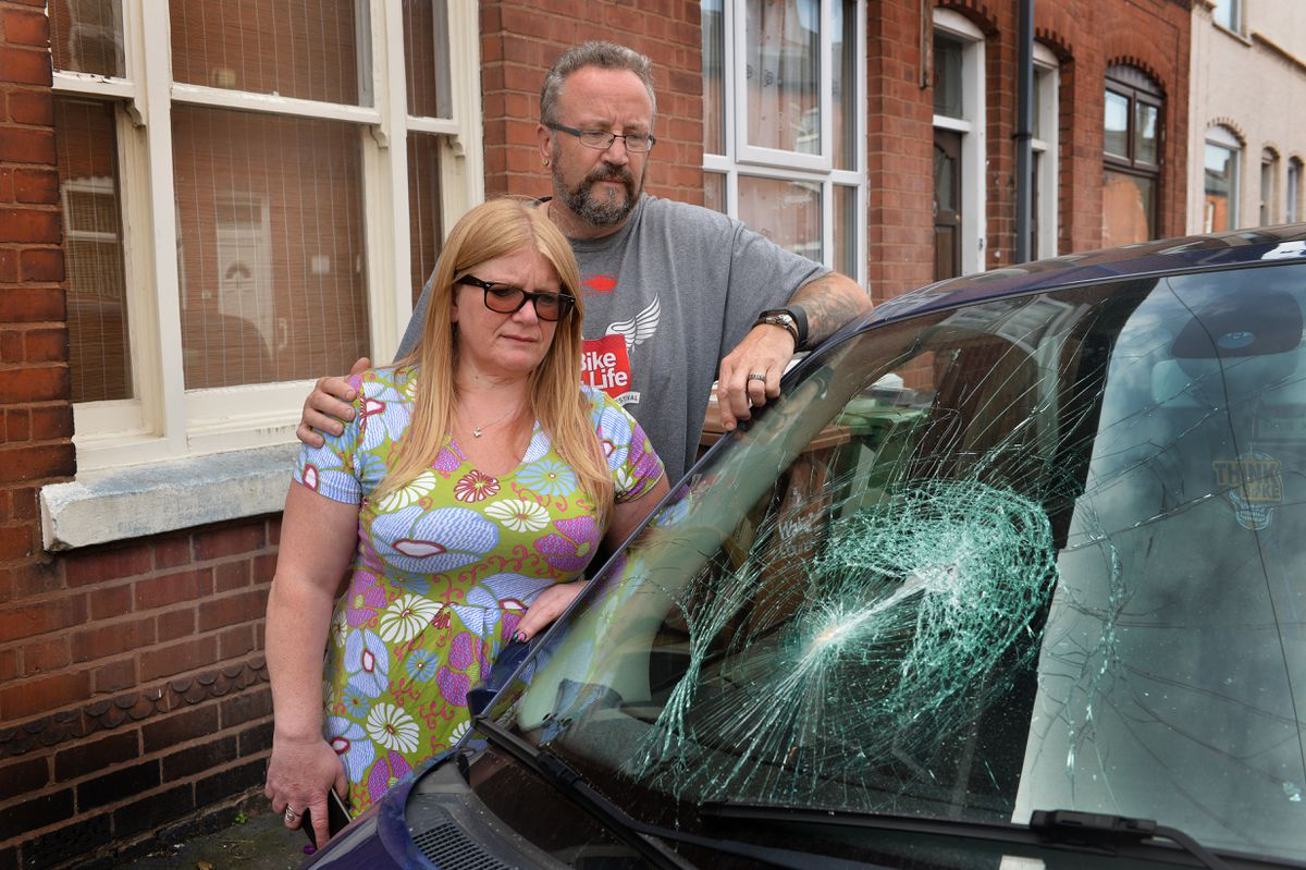 Sean Squires and his wife, Sarah Hunt-Squires, with one of their vandalised cars