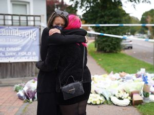 People hug at the scene near Belfairs Methodist Church in Eastwood Road North, Leigh-on-Sea, Essex, where Conservative MP Sir David Amess died after he was stabbed several times at a constituency surgery on Friday. Photo: Kirsty O'Connor/PA Wire