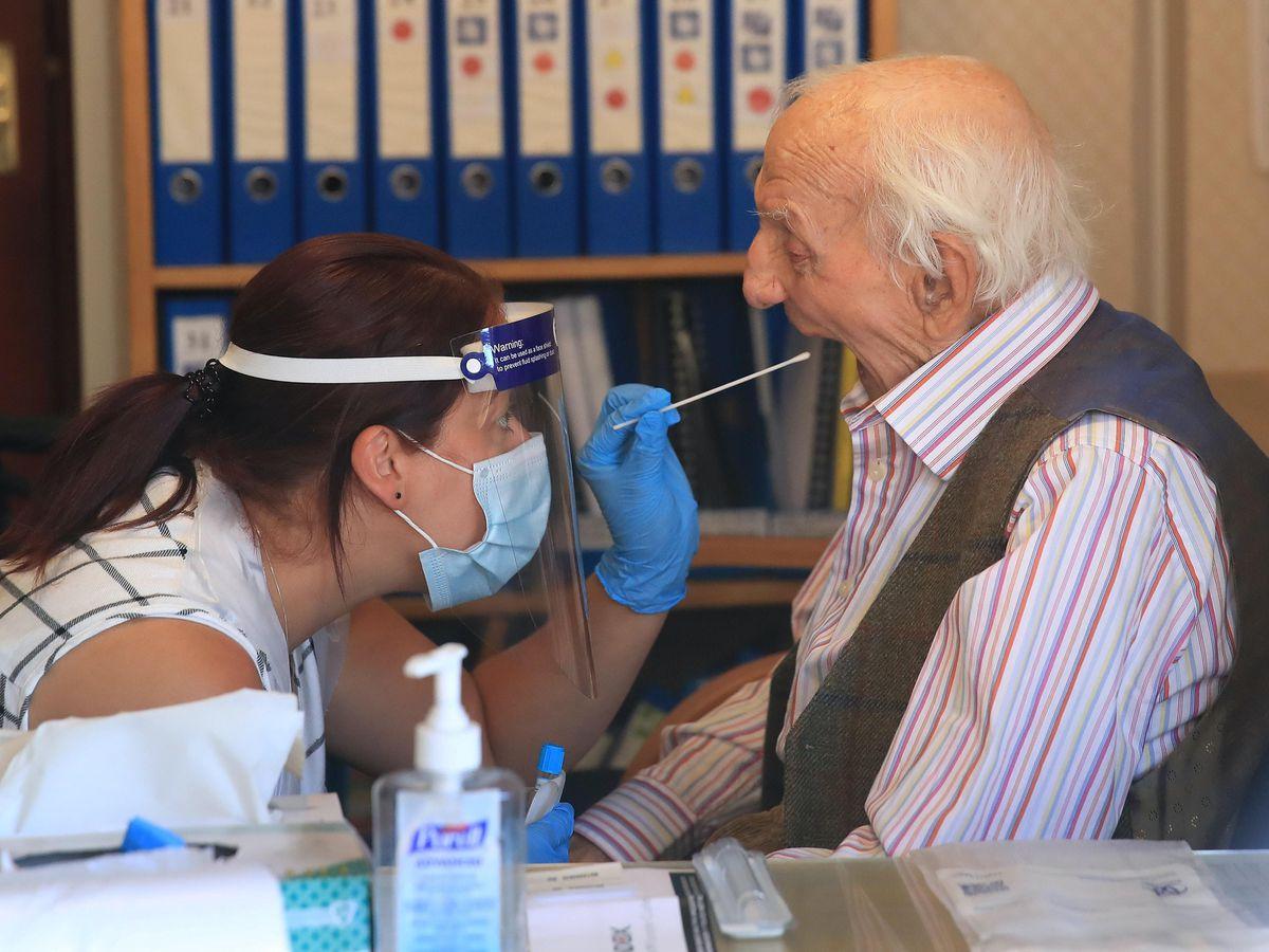 A care home resident undergoes a coronavirus swab test