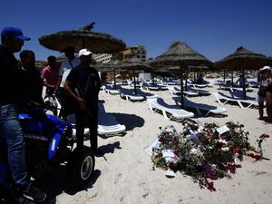 Police officers watch tourists taking photographs of flowers at the scene of the attack in Sousse, Tunisia