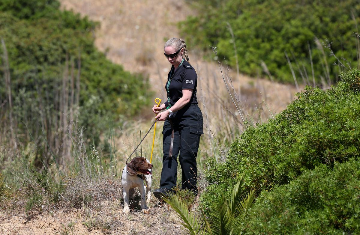 British police with sniffer dogs checking scrubland close to where Madeleine McCann went missing