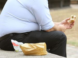 An overweight man eating fast food