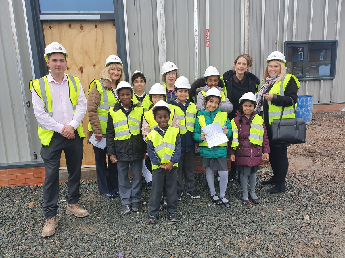 Josh Robinson - AMG site manager, Mrs Tolley with children Balraj, Arzoo, Alkianie, Samrawit, Parminder, Lewa, Daniel and Aliza Mrs Deakin (headteacher) and Mrs Amphlett with Councillor Joyce Underhill