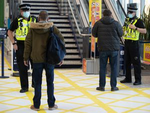 Police officers talk to commuters
